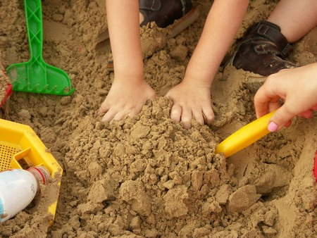 Child entertaining sowing of the sandpit. Hands of the child Stock Photo