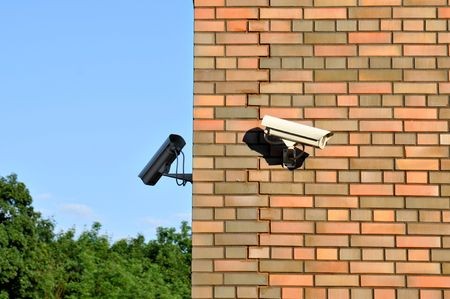 Two security cameras attached on the building. photo