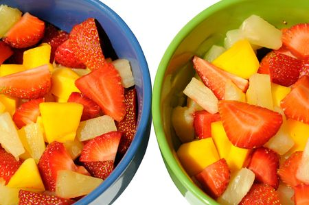 Two salad of fresh fruits: mango, peach, pineapple and strawberries with the whipped cream.