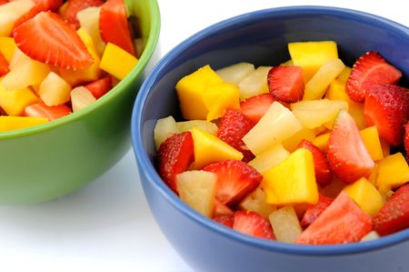 Two salad of fresh fruits: mango, peach, pineapple and strawberries.