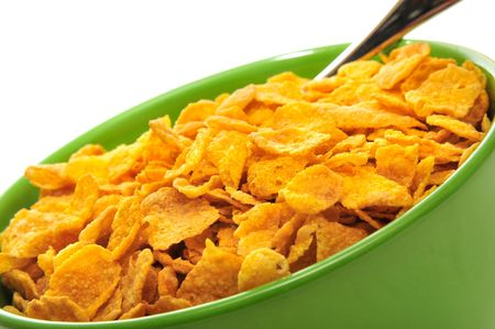 Cornflakes in the green bowl isolated on the white background. Stock Photo