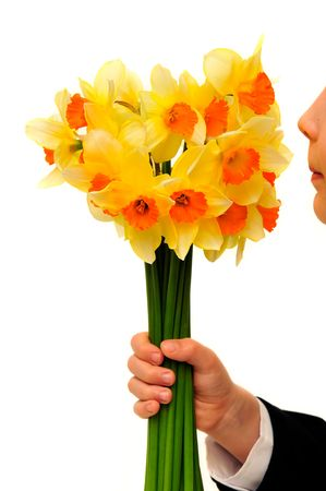 Boy with the bunch of daffodils isolated on the white background. Stock Photo