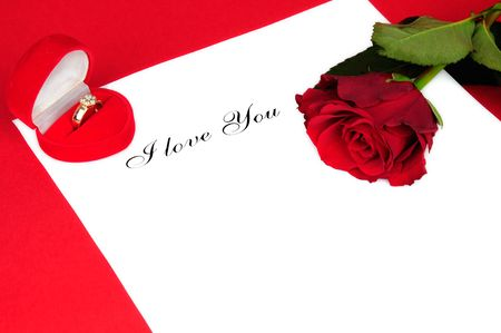 Gold ring, red rose and I love you on the white paper.  photo