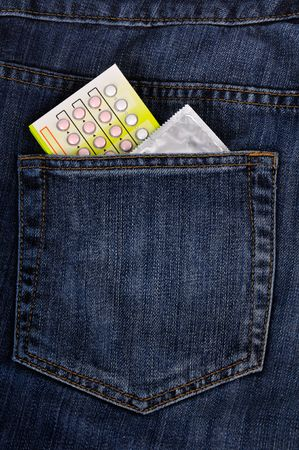 Condoms and contraceptive pills within back pocket. photo