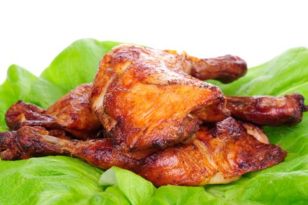 Baked chicken on the lettuce leaf isolated on the white background.