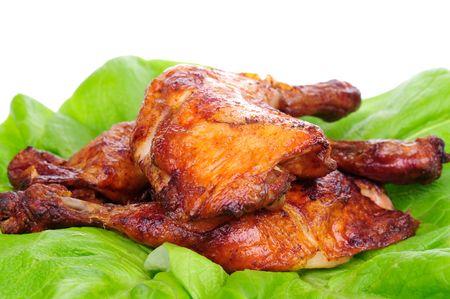 muslos: Pollo al horno en la hoja de lechuga aislada en el fondo blanco.