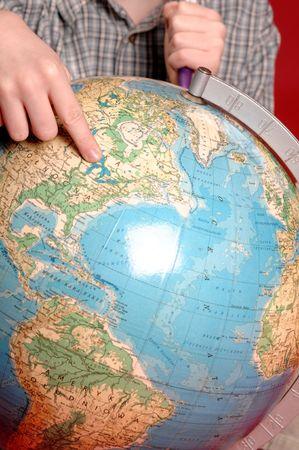 Child finger pointing on world globe. photo