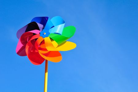 One multi-coloured windmill toy. Blue background.