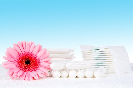 Health care and medicine - tampons and pads on blue background. photo