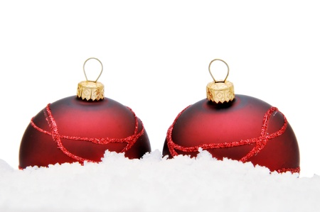 Two red glass balls on the snow. Stock Photo