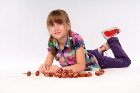 small articles: Little girl playing chestnuts