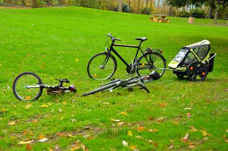 Bicycles and a trailer parked on a lawn at a picknic area.
