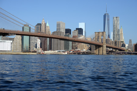 Brooklyn Bridge and Manhattan reflecting in East River Stock Photo