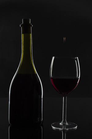 Butelka wina i kropla w szkle na ciemnym tle.
