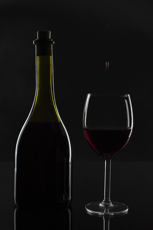 The bottle of wine and a drop in the glass on a dark background.