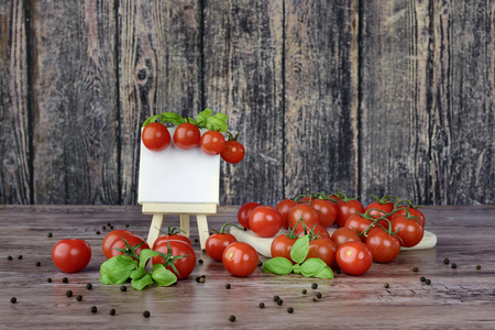 The canvas on the easel and scattered cherry tomatoes in rustic style.