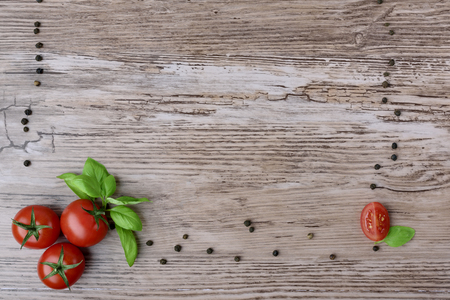 Pomidory i grupy papryki z li??mi bazylii na br?zowym drewnianym stole. Jako cz??? ramy widok z g�ry. Zdjęcie Seryjne