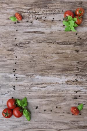 Pomidory i grupy papryki z li??mi bazylii na br?zowym drewnianym stole. Jako klatka, widok z g�ry.