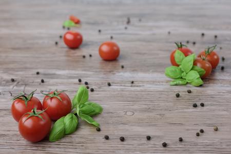 Rozrzucone pomidory czere?niowe i kulki papryki z li??mi bazylii na drewnianym stole.