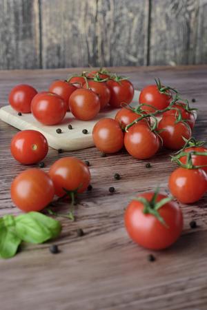 Rozrzucone pomidory czere?niowe z papryk? i li??mi bazylii na drewnianym, br?zowym stole z lekk? drewnian? desk?. Zdjęcie Seryjne
