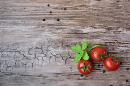 Trzy pomidory i grupy papryki z bazyli? na drewnianym stole, widok z g�ry. Zdjęcie Seryjne