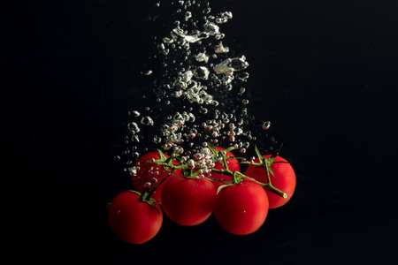 Tomatoes cherry in the water with air bubbles. Zdjęcie Seryjne