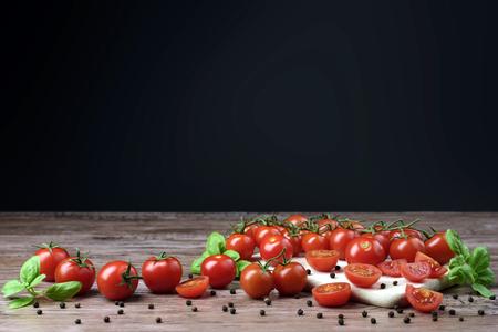 Rozproszone pomidory czere?niowe z li??mi bazylii na drewnianym stole. Zdjęcie Seryjne