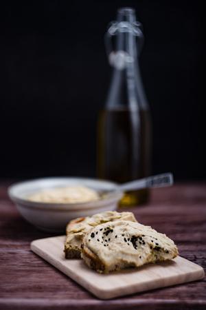 Hummus na chleb, oliwek w tle.