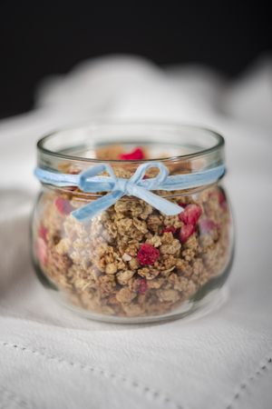Granola in jar with blue ribbon.