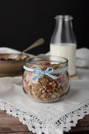Granola in a jar with blue ribbon, milk in bottle. It is stays on the white tablecloth.