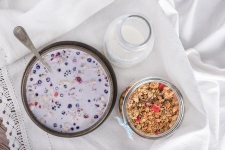 Br?zowy bowl z muesli w mleku, butelka mleka i granola w s?oiku. Widok z g�ry.