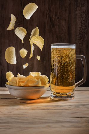 Beer and falling down crisps in golden light. Zdjęcie Seryjne