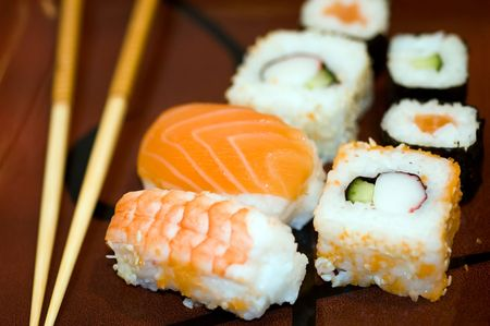 Prepared, delicious sushi and chopstics macro photo