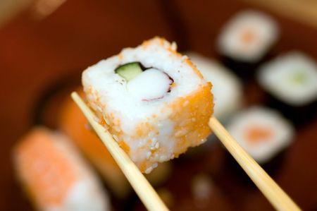 Sushi-roll with chopsticks restaurant photo