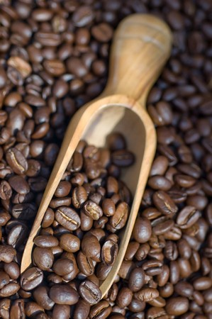 Close up of coffee beans spilling out of wooden scoop photo