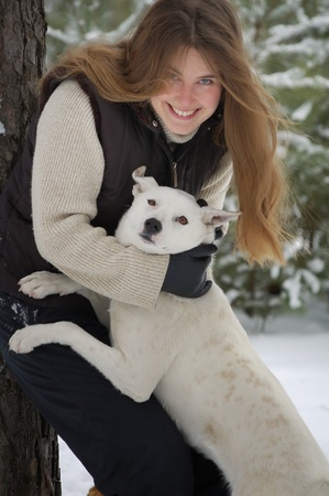 girl and a white dog in winter forest photo