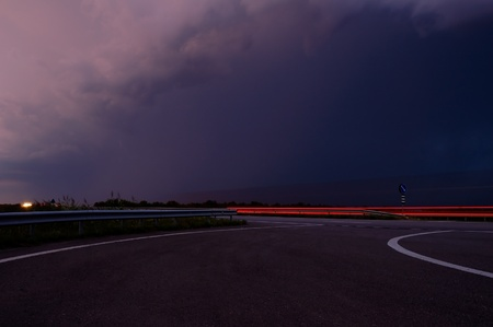 approaching thunderstorm with rain in the evening motorway Stock Photo - 10297980