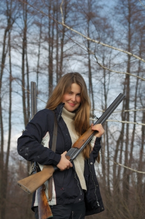 Woman hunter with two guns in the woods photo