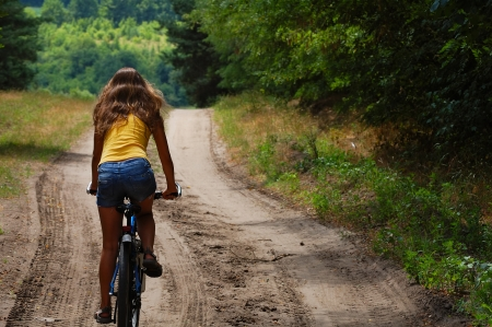 the girl with the bike for a walk in the woods on a sandy road photo