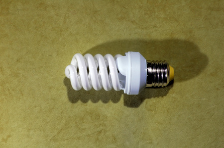 resourceful: A shiny spiral fluorescent light bulb with highlights and a silvertone base, on a green background
