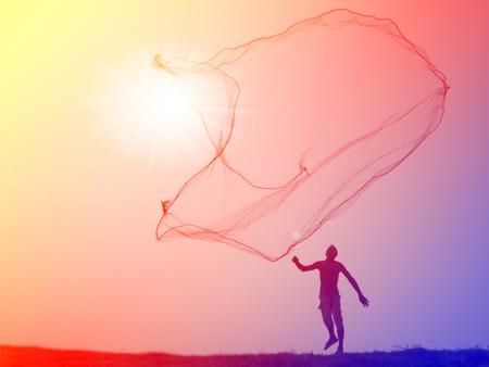 net fishing: Silhouette of traditional fishermen throwing net fishing lake at sunrise time . Stock Photo