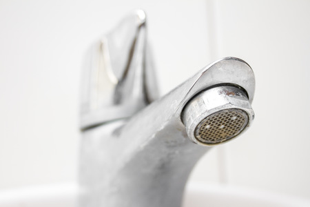 Modern style dirty faucet closeup view on white tiles background, small depth of field photo
