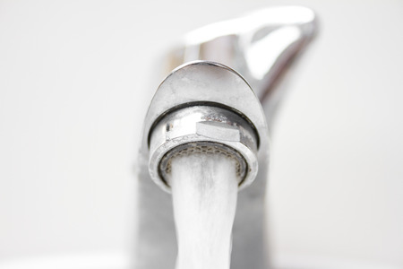 Front view of modern style opened dirty faucet closeup view with small depth of field Stock Photo
