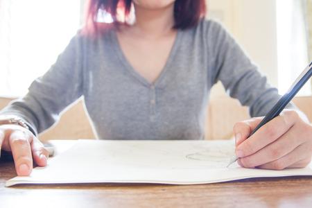Vrouw hand met potlood tekenen, schetsen op papier