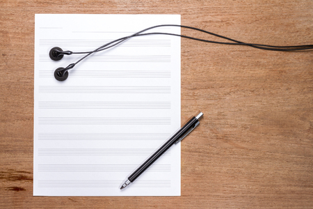sheet music background: blank sheet music on wooden table with headphones and pen Stock Photo