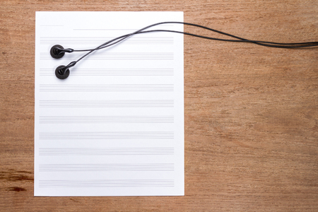 sheet music: blank sheet music on wooden table with headphones