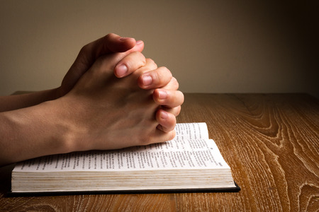 religious text: hands folded praying on bible