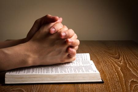 założonymi rękami modląc się na Biblii