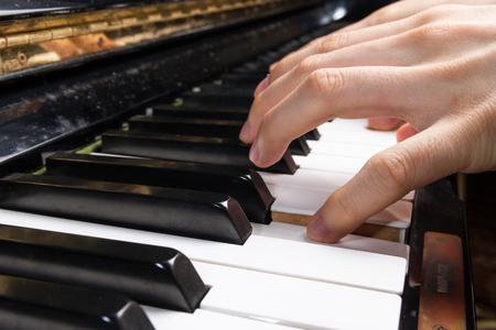 piano closeup: hand playing piano keyboard, closeup view