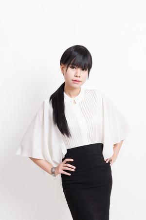 mani sui fianchi: asian donna di affari con le braccia sui fianchi isolato su sfondo bianco
